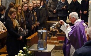 dad Pietro Segato, the parish priest of Casale Corte Cerro, waves incense facing a Moka cooking pot containing the ashes of Renato Bialetti, during their burial service in church of Casale Corte Cerro, Northern Italy